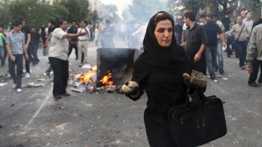 An Iranian woman carries rocks at a protest in Tehran during the 2009 Green Movement.