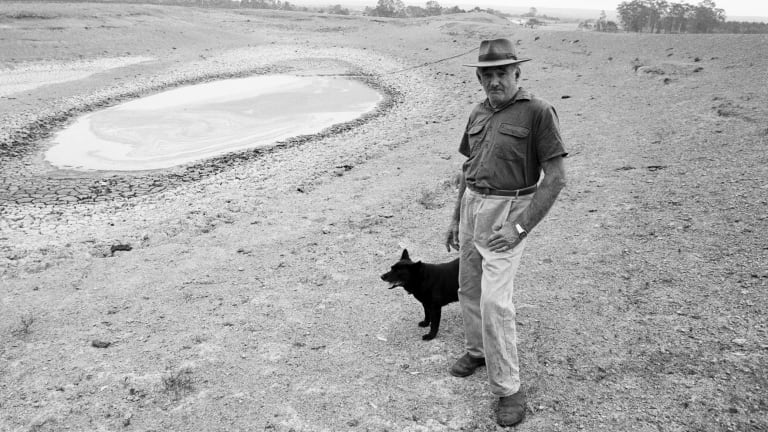 A Queensland farmer and his dog stand alongside a dried up dam in November 1994.