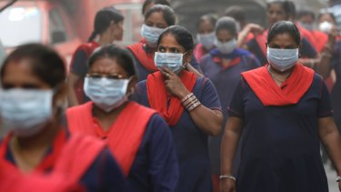 Women wear masks during an anti-pollution protest in New Delhi on Sunday.