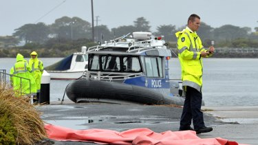 A police boat recovers three bodies after a plane crash at Ocean Grove.