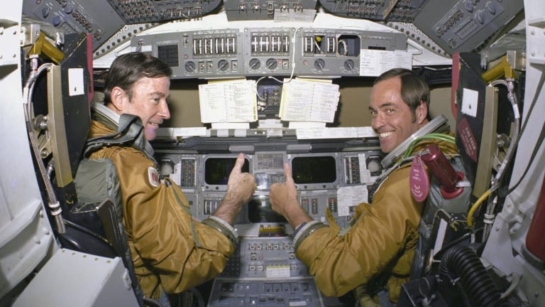 Astronauts for the first space shuttle mission, Commander John Young and Pilot Robert Crippen, take a break from their intensive training schedule to pose for pictures on the flight deck of the space shuttle Columbia in 1980.