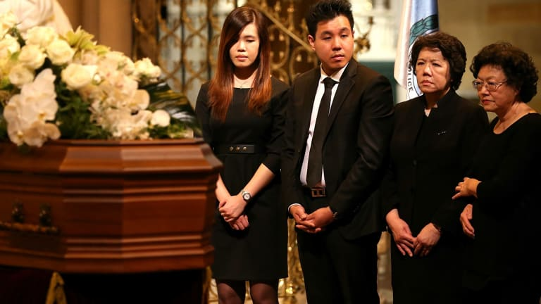 The family of Curtis Cheng stand by his coffin.