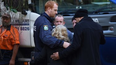 Detective Senior Constable Scott Craddock (left) and Detective Chief Inspector Gary Jubelin embrace Faye Leveson after bones were found.