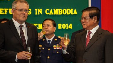 Australia's then immigration minister, Scott Morrison, and Cambodian Interior Minister Sar Kheng hold flutes of champagne after signing a deal to resettle refugees in Cambodia  on September 26, 2014, in Phnom Penh.