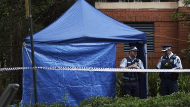 Police at the scene where a man's body was discovered in a charity clothing bin.