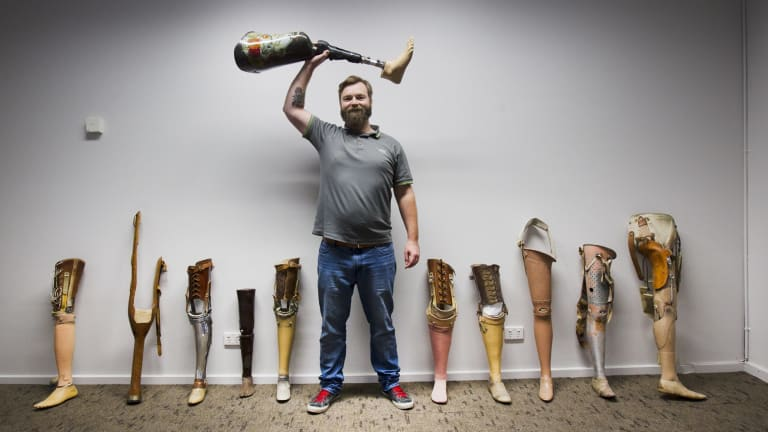 Karl Huttenmeister with many of the different styles of prosthetic legs made over the past century.