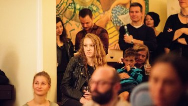 Party guests watch as Sally Seltmann performs.