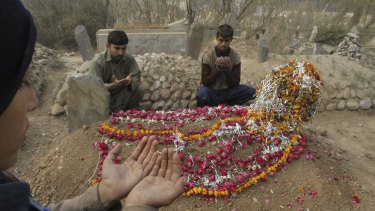 Condolences: Friends of a student killed in the attack offer prayers at his grave in Peshawar.