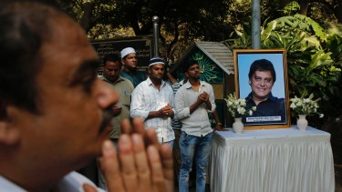 Friends and relatives offer prayers near a portrait of one of the victims during his funeral at a graveyard in Mumbai.
