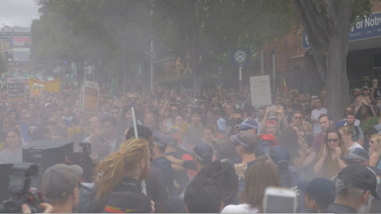 Haze from a fire extinguisher hangs over an Australia Day protest crowd on Broadway.