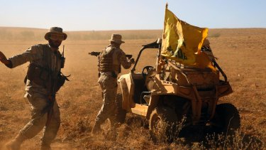 Hezbollah fighters stand near a four-wheel motorcycle near the Lebanon-Syria border.