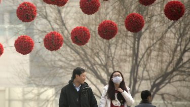 A woman wears a mask as she walks through Yuyuantan Park on a heavily polluted day in Beijing on Saturday.