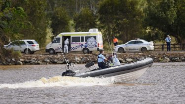 A police boat patrols on the Tweed River near Tumbulgum, where a three people are feared dead after their car was swept away on Monday.