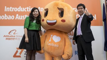 Bold move: Alipay International president Sabrina Peng  and Taobao's Tang Yongbo pose with the Taobao mascot at the launch.