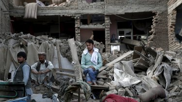 Men sit amid debris at the site a truck bomb blast in Kabul, on August 7, 2015.