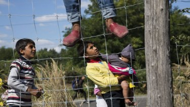 Children run from a collection point set up to transport refugees to camps in Morahalom, Hungary.