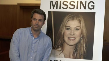 Ben Affleck in <i>Gone Girl</i>, with a poster of his missing wife.