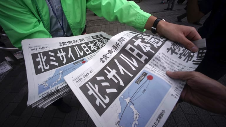 A man, left, distributes an extra edition of a newspaper reporting about North Korea's missile launch, at Shimbashi Station in Tokyo.