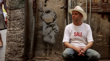 Street art expert Andrew McDonald next to an original Banksy in one of Melbourne's lanes.