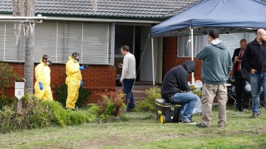Police search a house in Georges Hall after a drug raid on Wednesday.
