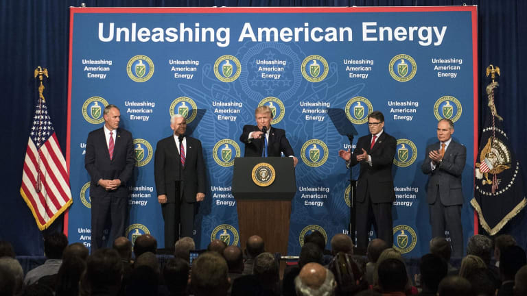 """US President Donald Trump, centre, speaks during the Unleashing American Energy event at the Department of Energy,  as he seeks to reorient the government away from fighting climate change and toward American """"energy dominance""""."""
