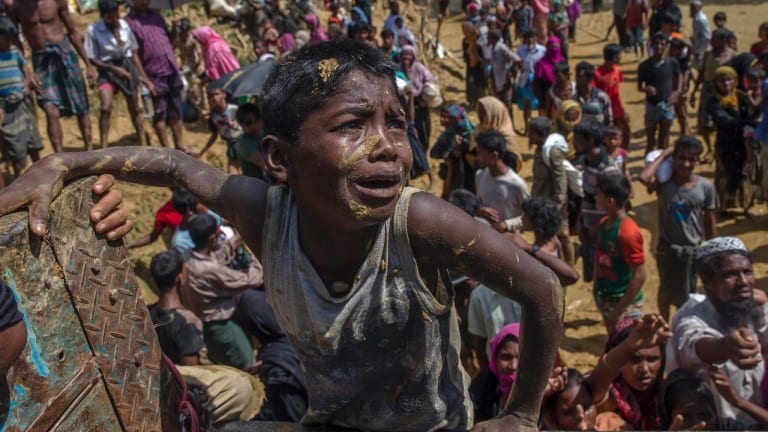 A Rohingya Muslim boy, who crossed over from Myanmar into Bangladesh, pleads with aid workers to give him a bag of rice.
