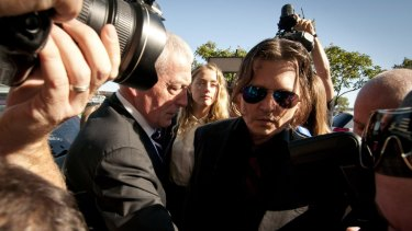 Amber Heard and her husband, actor Johnny Depp, work their way through a media scrum outside Southport Magistrates Court.