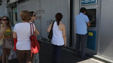 Athenians continue to queue at cash machines at banks.