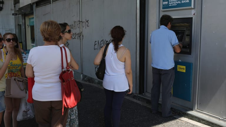 Athenians continue to queue at cash machines at banks.