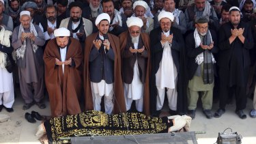 Afghan men offer funeral prayers behind the body of civilian killed in Friday night's suicide attack at the Shiite mosque.