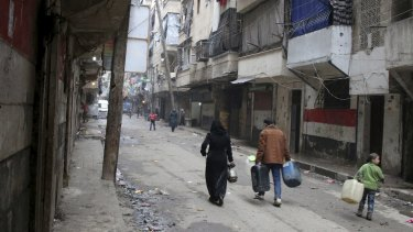 Civilians walk with containers for fuel and water in Aleppo, Syria in this photo from February, 2016.