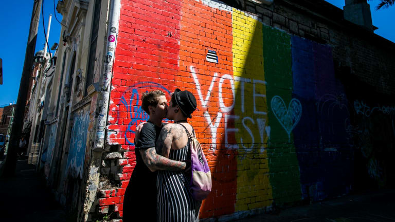 "A couple embrace to celebrate the ""yes"" verdict of Australia's postal vote on same-sex marriage in Newtown."