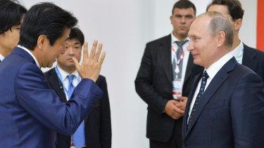 Mr Abe speaks to Mr Putin at the forum.