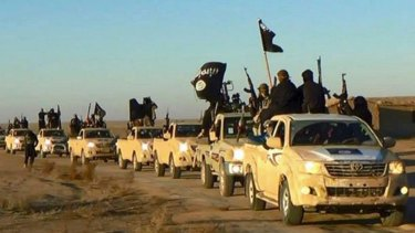 Islamic State hold up weapons and wave flags on their vehicles in a convoy in Syria.