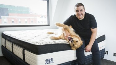 OzMattress owner Stefan Papas with his dog Mac on one of the mattresses manufactured by his company.