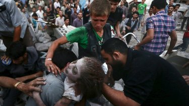 Men hold an injured girl rescued from a site hit by what activists said was heavy shelling by regime forces in the Douma district of Damascus.