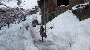 An Afghan girl carries shovels to dig out the snow.