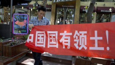 """A worker of a restaurant bar puts up a banner which partly reads: """"South China Sea is China's territory"""" in Beijing."""