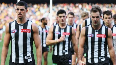 Heavy defeat: Scott Pendlebury and the Magpies leave the field.