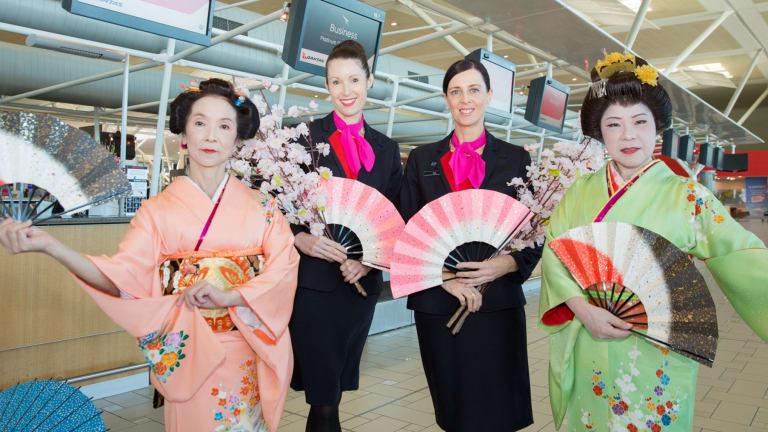 Qantas staff celebrating flights into Asia at Brisbane Airport.
