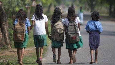 Schoolgirls walk to a school at Burha Mayong village east of Gauhati, India.