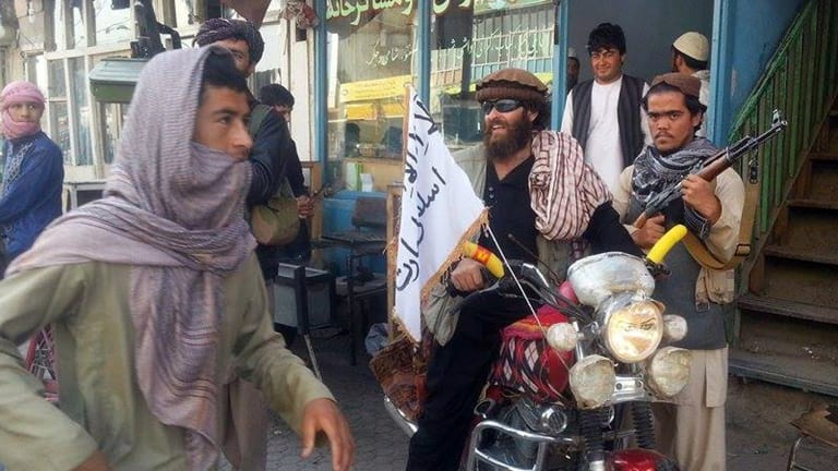 A Taliban fighter sits on his motorcycle adorned with a Taliban flag in a street in Kunduz, Afghanistan, in September.