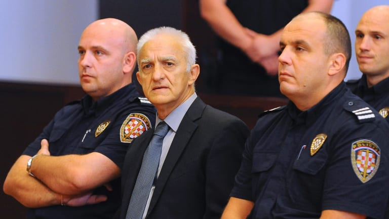 Dragan Vasiljkovic, center, sits between two guards in a courtroom at the beginning of his trial.