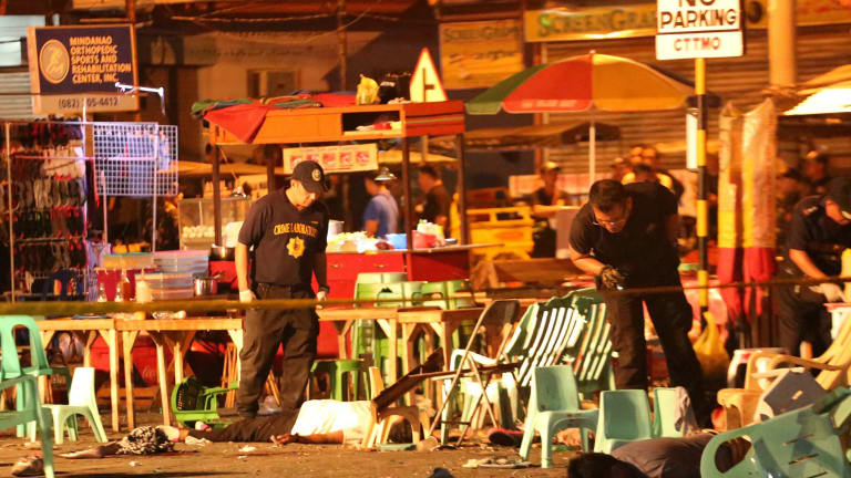 Police officers at the scene of an explosion at a night market in Davao city on Friday night.