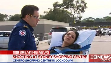 A woman is wheeled away by paramedics after the shooting at Bankstown Central Shopping Centre.