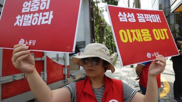 A protester outside the court in Seoul demonstrates against the Samsung executives.