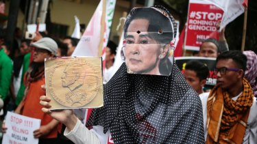 A Muslim woman wears a mask of Myanmar's Foreign Minister Aung San Suu Kyi during a rally against the persecution of Rohingya Muslims last month.