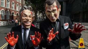 Demonstrators dressed as former British prime minister Tony Blair and former US president George Bush Jr outside the Queen Elizabeth II conference centre in London.