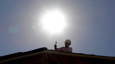 A roof repairer works under the midday sun in Gilbert, Arizona.
