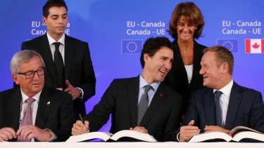 Canadian Prime Minister Justin Trudeau, centre, signs the trade deal with European Commission president Jean-Claude Juncker, left, and European Council president Donald Tusk, right.